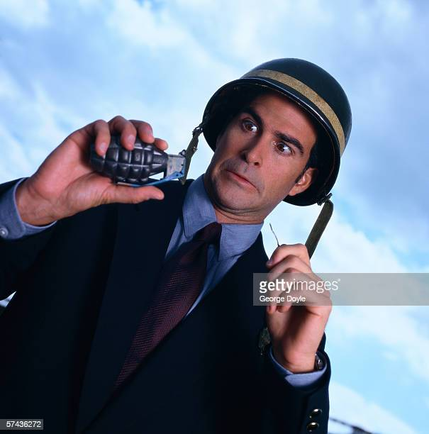low angle close-up of a businessman wearing a bomber helmet and holding a grenade - hand grenade stock pictures, royalty-free photos & images