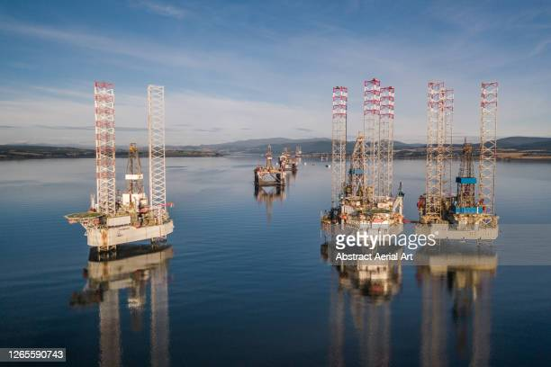 low angle drone shot showing the reflections of various oil drilling rigs in a calm ocean channel, cromarty firth, scotland, united kingdom - abandoned stock pictures, royalty-free photos & images