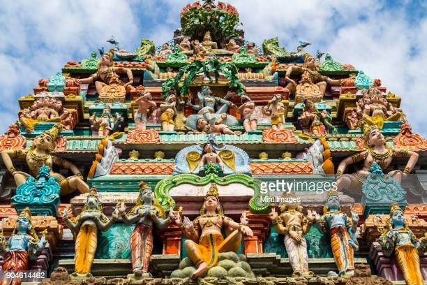 low angle exterior view of facade of hindu temple decorated with colourful sculptures. - hinduism bildbanksfoton och bilder