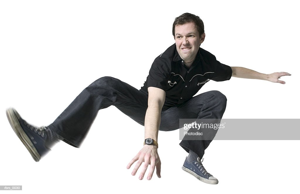 low angle full body shot of a young adult male in a black shirt as he jumps up in the air : Foto de stock