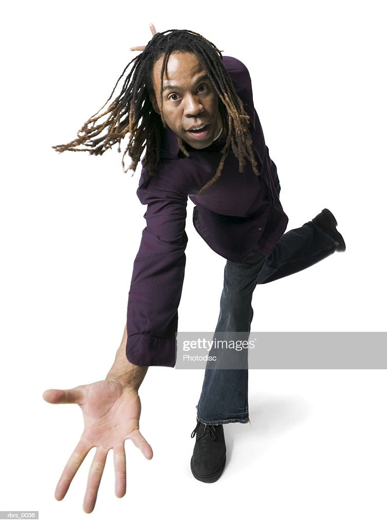 low angle full body shot of a young adult male in a purple shirt as he strikes a fun pose : Foto de stock