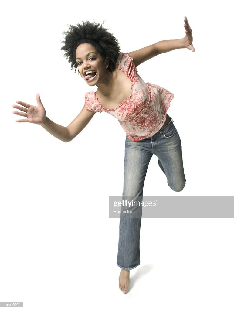 low angle full body shot of a young adult woman as she playfully jumps around : Foto de stock