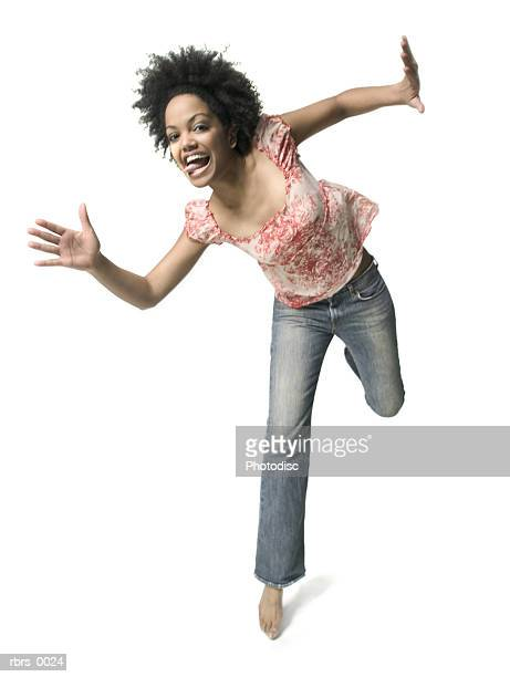 low angle full body shot of a young adult woman as she playfully jumps around