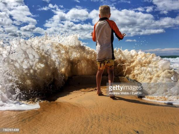Low Angle Full Length Of Boy Playing By Water At Beach On Sunny Day
