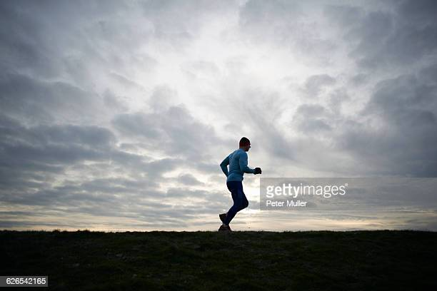 Low angle full length side view of runner against dramatic sky