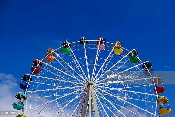 low angle image of a ferris wheel against a blue sky - reuzenrad stockfoto's en -beelden
