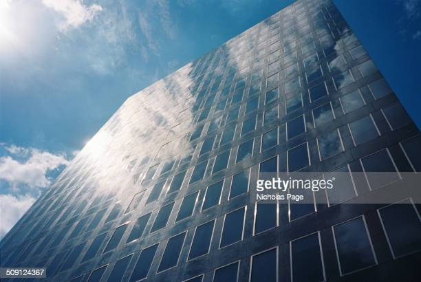 Low angle image of a tall glass office block. Blue sky and white clouds are reflected on the gleaming surface.