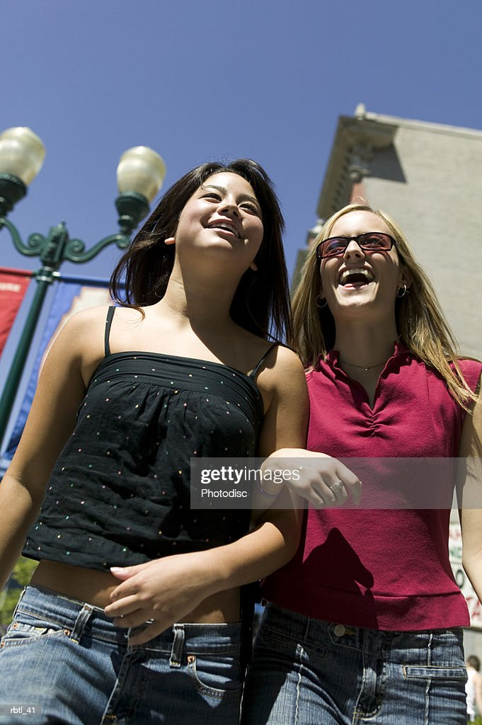 low angle lifestyle portrait of two teenage female friends as they stroll down the sidewalk together : Foto de stock