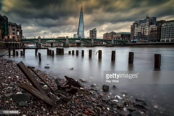 Low angle long exposure looking along the River Thames and back at the newly build Shard at London Bridge. It's sunset and the stormy looking skies...