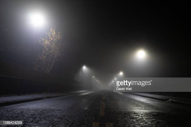low angle, looking up at a road and street lights on an atmospheric foggy winters night. uk. - fog stock pictures, royalty-free photos & images
