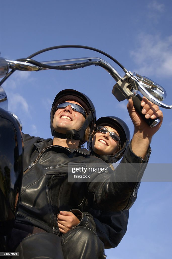 Low angle looking up to a couple sitting on their motorcycle ready to ride : Stock Photo