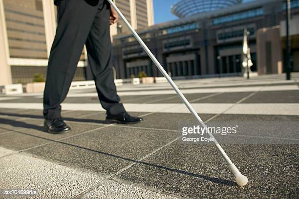 low angle low section view of a blind man walking with the aid of a white stick