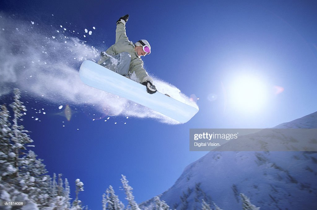Low Angle Mid Air Shot of a Woman Snowboarding : Stock Photo