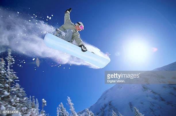 low angle mid air shot of a woman snowboarding - wintersport stock-fotos und bilder