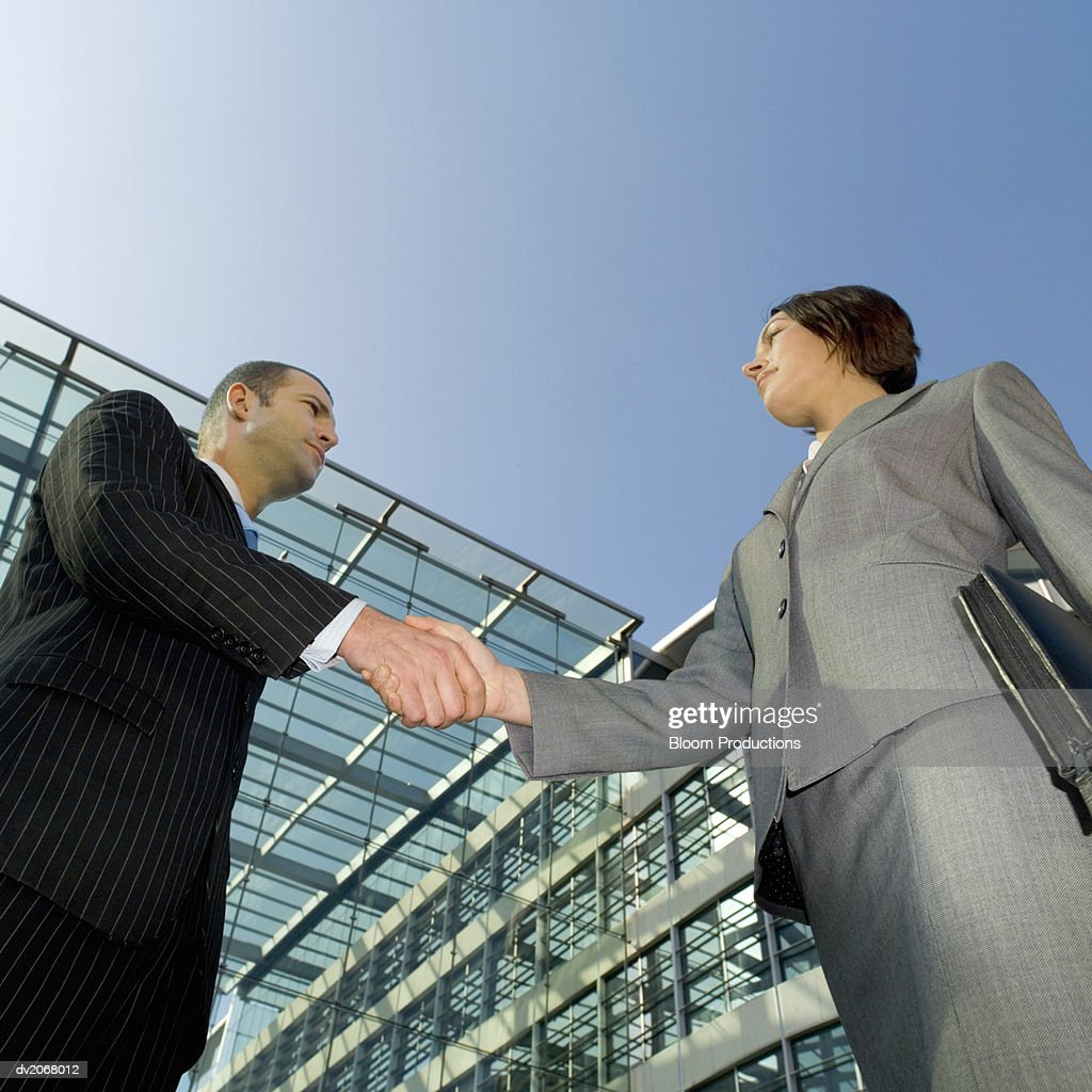 Low Angle of a Businessman and Businesswoman Shaking Hands : Stock Photo