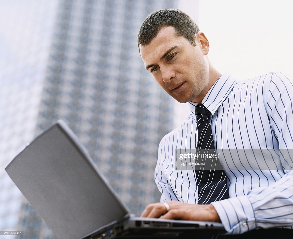 Low Angle of a Businessman Using a Laptop Computer Outdoors in a City : Stock Photo