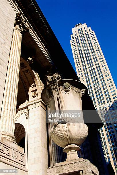 Low angle of a large urn at the New York Public Library with a skyscraper in the background.