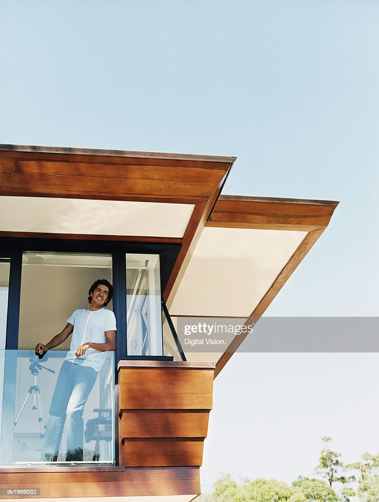 Low Angle of a Man Standing Behind the Front Door of His Wooden House : Stock Photo