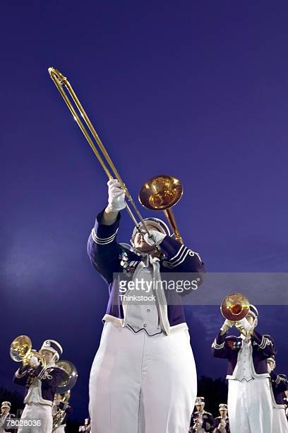 low angle of a marching band member playing his trombone. - marching band stock pictures, royalty-free photos & images
