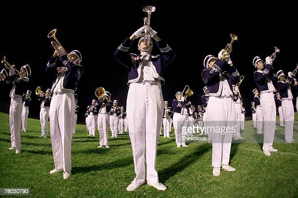 Low angle of a marching band performing on the field, close-up on the trumpet section.