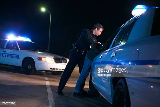 Low angle of a police officer making an arrest, bending the suspect over the hood of his police car