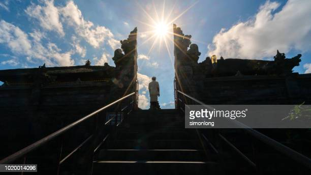 low angle of a standing man in temple against sky - denpasar stock pictures, royalty-free photos & images