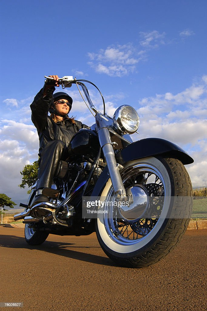 Low Angle Of A Woman In Leather Riding A Motorcycle Stock