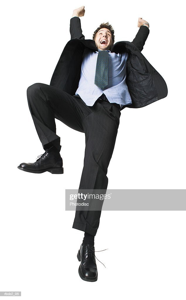 low angle of a young caucasian man in a suit as he throws up his arms in celebration : Foto de stock