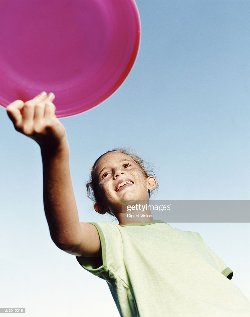 Low Angle of a Young Girl Holding a Pink Frisbee : Stock Photo