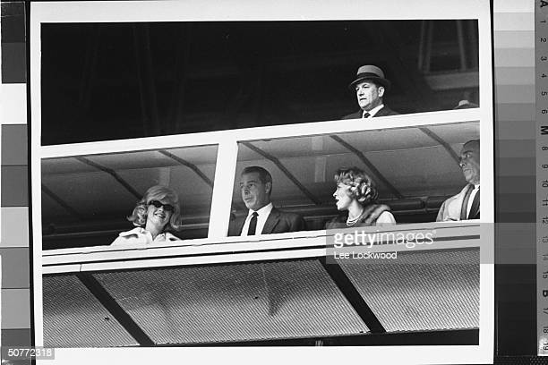 Low angle of actress Marilyn Monroe exhusband baseball player Joe DiMaggio watching opening game at Yankee Stadium from window in clubhouse