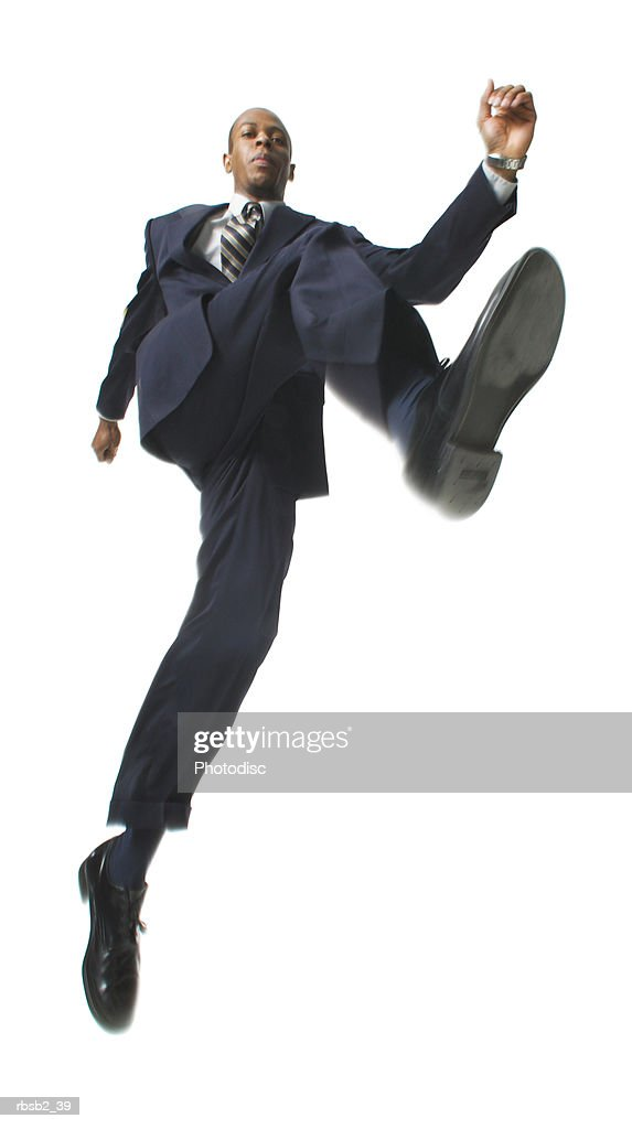 low angle of an african american business man in a dark suit as he jumps through the air : Foto de stock