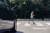 Low angle of car in front of pedestrian crossing and walking boy with smartphone