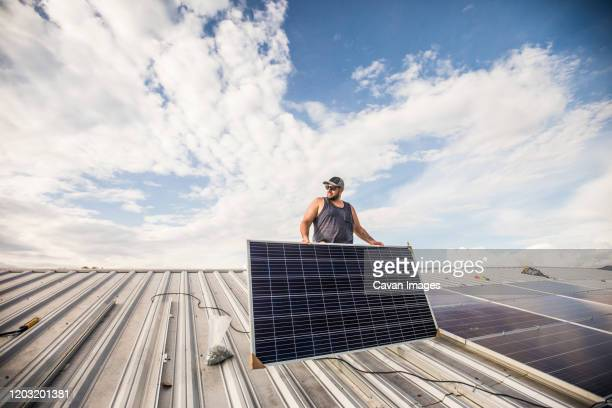 low angle of construction worker installing solar panels on roof. - initiative stock pictures, royalty-free photos & images