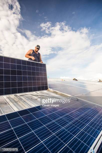 low angle of electrician installing solar panels on roof. - steuerpult stock-fotos und bilder