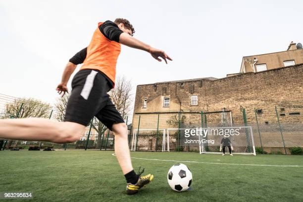 low angle of male footballer about to take a shot at goal - amateur stock pictures, royalty-free photos & images