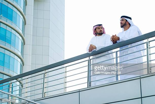 Low angle of men in traditional Middle Eastern dress standing at balcony, Dubai, UAE