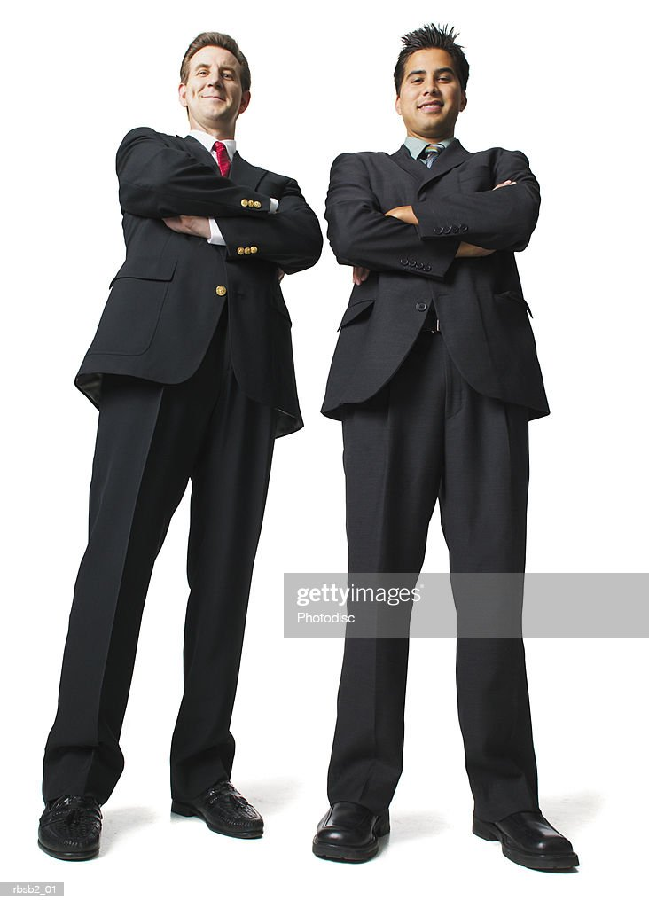 low angle of two business men in suits as they fold their arms and smile : Foto de stock