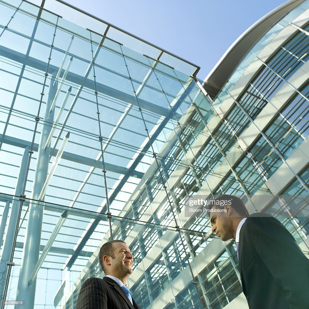 Low Angle of Two Businessmen Talking Outside a Glass Building : Stock Photo