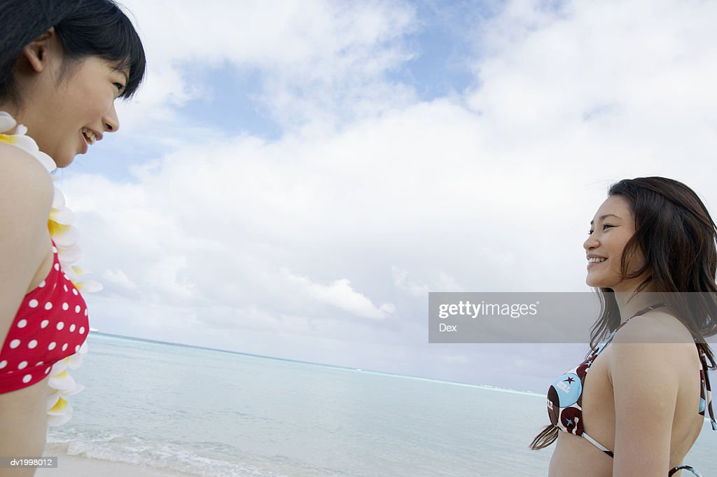 Low Angle of Two Women in Bikinis Standing by the Sea, Talking : Stock Photo