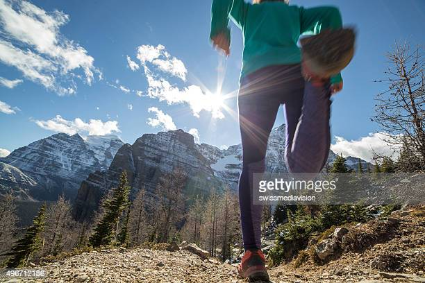 Low angle of woman running downhill towards sunlight