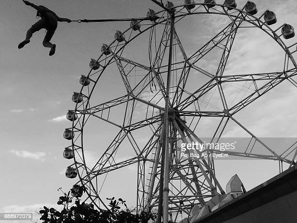 Low Angle Person Swinging Into Sky And Ferris Wheel