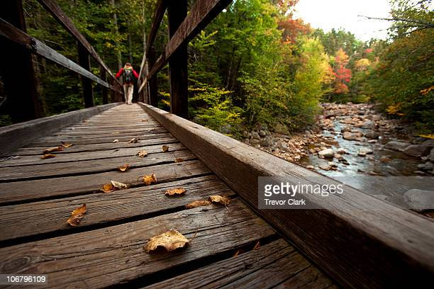 Low angle perspective of one man hiking across a wooden bridge with a stream and fall leaves in view.