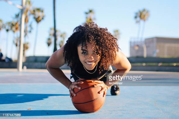 low angle portrait of a young women doing push ups on a basketball in venice, california - basketball sport stock pictures, royalty-free photos & images