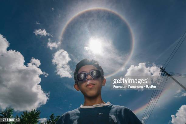Low Angle Portrait Of Boy Wearing Sunglasses Standing Against Sky During Sunny Day