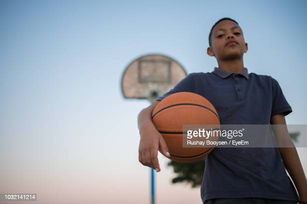 Low Angle Portrait Of Boy With Ball Standing On Basketball Court Against Sky