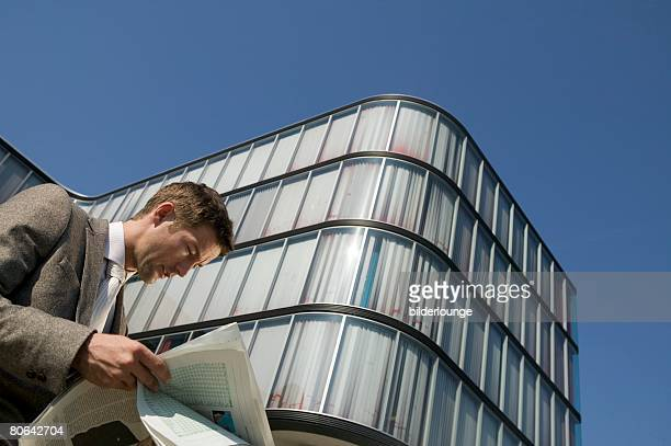 low angle portrait of businessman reading newspaper in front of office building