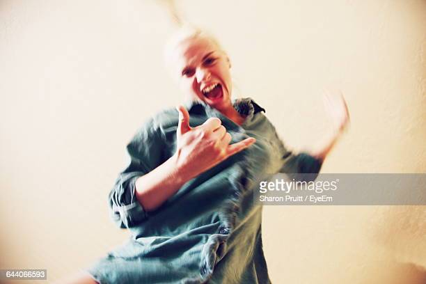 Low Angle Portrait Of Cheerful Young Woman Dancing Against Wall