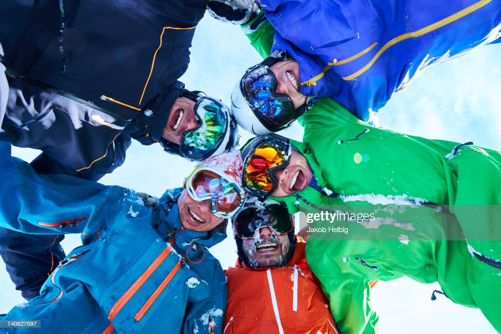 Low angle portrait of circle of skiers in helmet and goggles, Aspen, Colorado, USA : Stock Photo