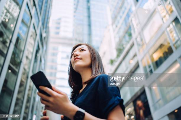 low angle portrait of confidence and successful young asian businesswoman with coffee to go, using smartphone while standing against highrise corporate buildings in financial district in the city - motivation stock pictures, royalty-free photos & images