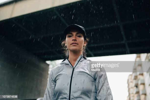 low angle portrait of female athlete standing against bridge during rainy season - low angle view stockfoto's en -beelden